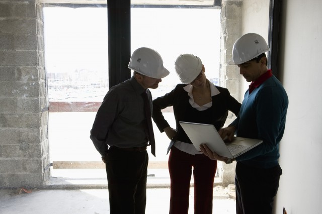 a property developer and two business owners signing a commercial real estate lending agreement