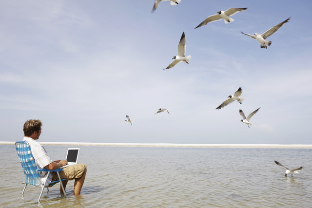 man using his laptop on the beach for online banking